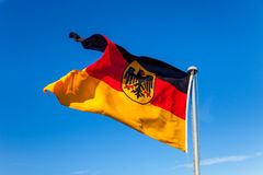 Germany flag on blue sky. The German national flag flying in the wind royalty free stock photo
