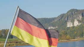 Germany flag close up. Big flag of Germany against river and mountains stock video footage