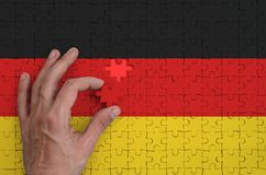 Germany flag is depicted on a puzzle, which the man`s hand completes to fold.  stock illustration