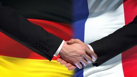 Germany and France handshake, international friendship relations flag background. Stock footage stock video