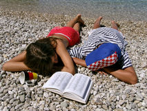 Germany girl and Croatian boy lying on stone beach. Germany girl and Croatian boy (best friends) lying on the pebbles beach and watch each other with dictionary Royalty Free Stock Image