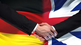 Germany and Great Britain handshake, international friendship, flag background. Stock footage stock video footage