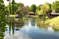 Germany.Heide Park resort in Soltau. View on the lake and stylized boats on rafts of logs loating on the lake.Photo was taken in May 2015 Stock Images