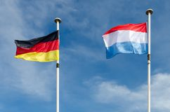 Germany and luxembourg flags. A germany and luxembourg flags are floating in a blue sky Stock Image