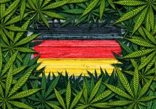 Germany Marijuana Symbol. Germany marijuana and German cannabis symbol with the flag on rustic wood with leaves as a border in a 3D illustration style Stock Images