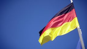 Germany national flag. Against the blue sky. Slowmotion from a 120 fps original shoot stock video