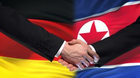 Germany and North Korea handshake, international friendship, flag background. Stock footage stock video