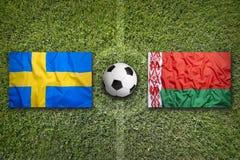 germany sweden vs Vitryssland flaggor på fotbollfält Arkivbild