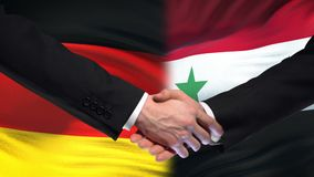 Germany and Syria handshake, international friendship relations, flag background. Stock footage stock video