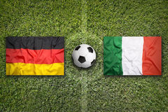 Germany vs. Italy flags on soccer field Royalty Free Stock Image