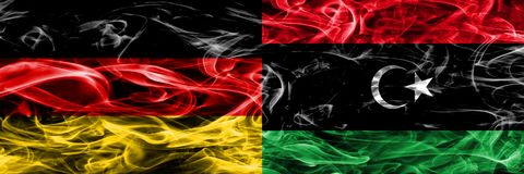 Germany vs Libya smoke flags placed side by side. German and Lib. Ya flag together royalty free illustration