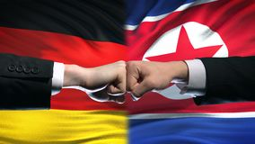 Germany vs North Korea conflict, fists on flag background, diplomatic crisis. Stock footage stock video footage