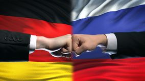 Germany vs Russia conflict, international relations, fists on flag background. Stock footage stock footage
