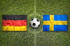 Germany vs. Sweden flags on soccer field Stock Photo
