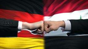 Germany vs Syria conflict, international relations, fists on flag background. Stock footage stock video footage