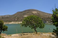 Germasogeia Dam Seen Through A Single Tree With A Bench Underneath It Royalty Free Stock Images