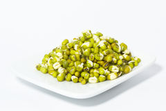 Germinated beans. Germinated seeds of legumes (soybeans) on a white saucer.  White background Stock Photo