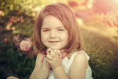 Germination and growth. Innocence, purity and youth concept. Child sitting at blossoming rose flowers on green grass. Girl smiling with folded hands in summer Royalty Free Stock Photo
