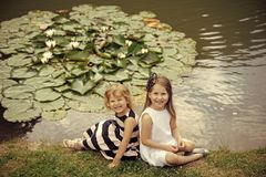 Germination and growth. Girls sit on grass at pond with water lily flowers. Future and flourishing. Children happy smile on green lake landscape. Summer Royalty Free Stock Image