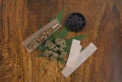 Germogli sativa della foglia e di fiore dell'erbaccia della cannabis su fondo di legno con la smerigliatrice e le grandi carte di Immagine Stock Libera da Diritti