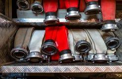 Gerolde brandslangen, die in rijen, in het handschoenenkastje van de brandvrachtwagen worden geschikt stock afbeeldingen