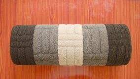 Gerolde die yogamat na oefening op rustieke houten vloerachtergrond wordt ge?soleerd in een centrum van de sportactiviteit De ges