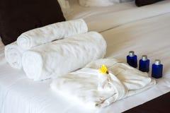 Gerolde handdoeken en badjas op bed royalty-vrije stock foto