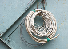 Gerolde kabels op de achtergrond van oude metaalmuur Stock Foto