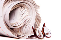 Gerolde kranten en lezingsglazen stock foto's