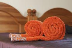 Gerolde oranje handdoeken op het violette behandelde bed Stock Fotografie