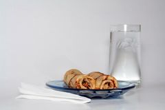 Gerolde pannekoeken met aardbeijam en een glas water Royalty-vrije Stock Foto