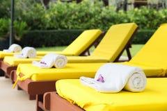 Gerollt herauf Tücher auf gelben sunbeds im Pool am Erholungsort Stockbild