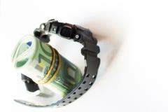 Gerollt von hundert Euroanmerkungen innerhalb des verschlossenen Gurtes der modernen Armbanduhr lokalisiert auf weißem Hintergrun stockbild