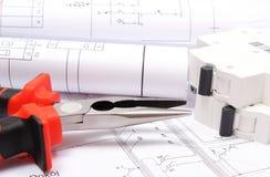 Gerollte elektrische Diagramme, elektrische Sicherung und Arbeitswerkzeuge auf Bauzeichnung des Hauses Lizenzfreie Stockfotos