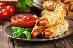 Gerollte Hotdogwürste gebacken im Blätterteig Lizenzfreies Stockfoto