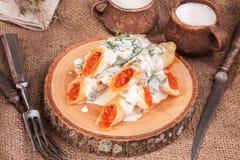 Gerollte Krepps mit Kaviar und Schale Milch Stockbild