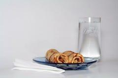 Gerollte Pfannkuchen mit Erdbeeremarmelade und einem Glas Wasser lizenzfreies stockfoto