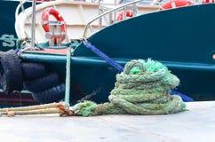 Gerolltes grünes Seeseil gegen die festgemachte Yacht stockfotografie