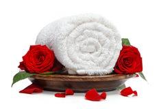 Gerolltes weißes Tuch und Rosen und rosafarbene Blumenblätter Stockbilder