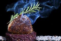 Gerookt kalfsvleeslendestuk met sesam en rozemarijn op een bed van zoute en donkere achtergrond stock fotografie