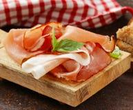 Gerookte ham jamon (Parma) met basilicumbladeren Stock Fotografie
