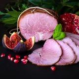 Gerookte ham met kruiden, vruchten granaatappel op zwarte achtergrond Stock Foto