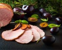 Gerookte ham met kruiden, vruchten plumps op zwarte achtergrond Royalty-vrije Stock Afbeeldingen