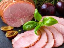 Gerookte ham met kruiden, vruchten plumps op zwarte achtergrond Royalty-vrije Stock Fotografie