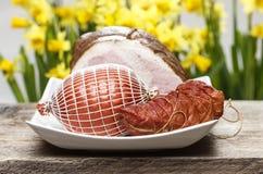 Gerookte ham op houten lijst Gele gele narcissen op de achtergrond Stock Fotografie