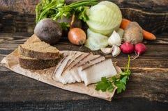 Gerookte reuzel met brood en groenten op de achtergrond Houten plattelander stock foto