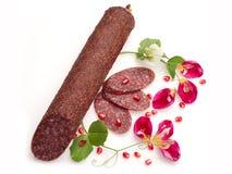 Gerookte salami met bloemen en granaatappel Stock Afbeeldingen