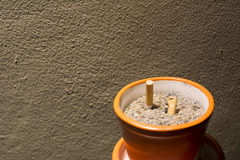 Gerookte sigaretten in asbakje op nacht Stock Afbeelding