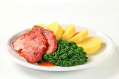 Gerookte varkensvleeshals met aardappelbollen en spinazie stock foto