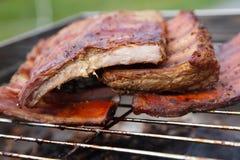 Gerookte varkensvleesribben op een rokersgrill Royalty-vrije Stock Afbeeldingen